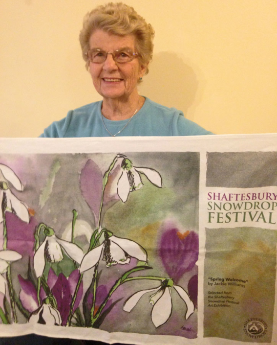 Jackie Williams with Her image on a tea towel - Shaftesbury Snowdrops
